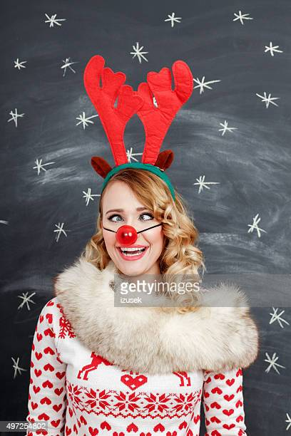 Woman in winter outfit and reindeer antlers headband making squint