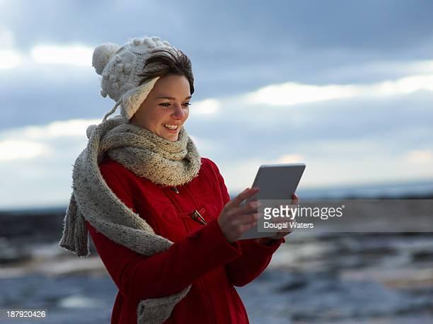 Woman in Winter wear using digital tablet.