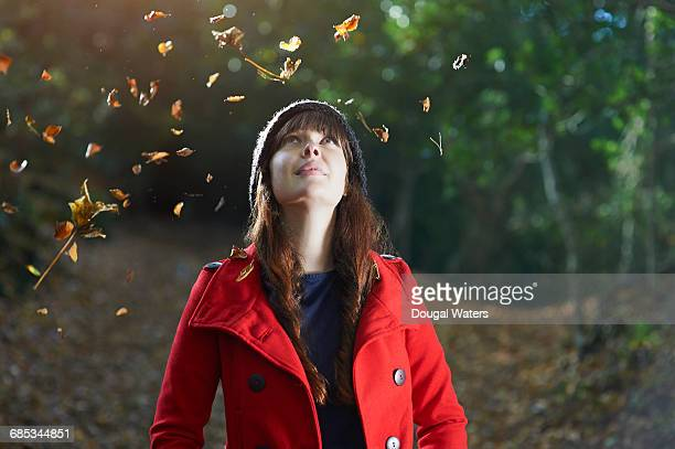 Woman in woodland looking up toward falling leaves