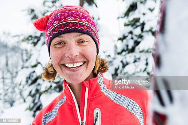 Woman in Wool Ski Hat Smiling at Camera with Snow