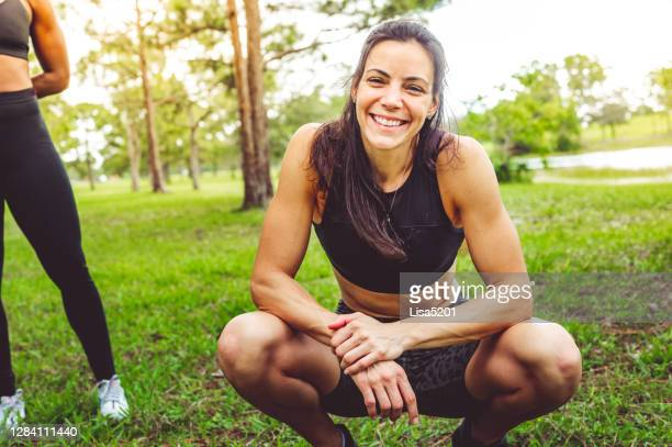 woman in workout clothes looks at the camera in a candid relaxed portrait - mid adult stock pictures, royalty-free photos & images
