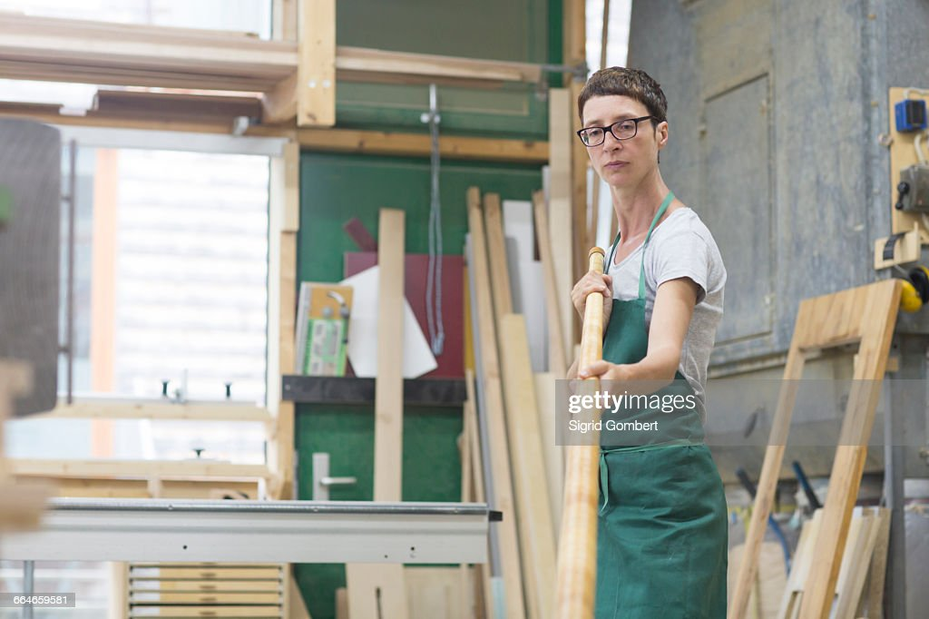 Woman in workshop checking alphorn tube : Stock-Foto