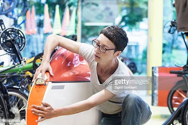 woman in workshop checking recumbent bicycle bodywork - sigrid gombert stockfoto's en -beelden