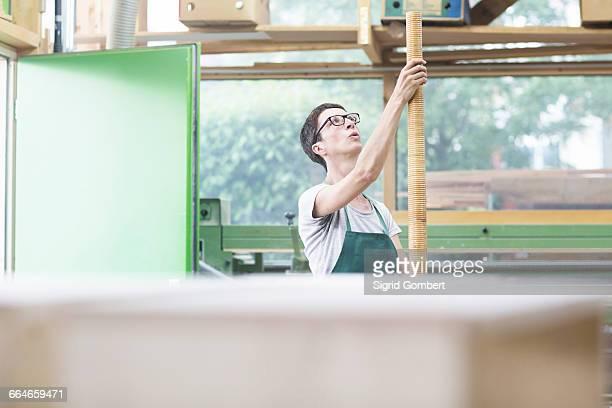 woman in workshop holding alphorn - sigrid gombert stockfoto's en -beelden