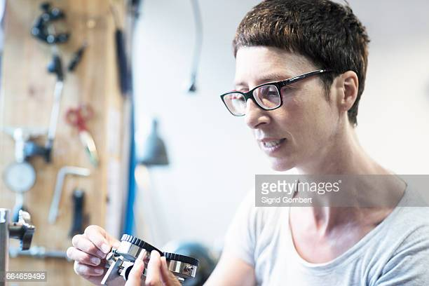 woman in workshop looking at bicycle part - sigrid gombert stock pictures, royalty-free photos & images