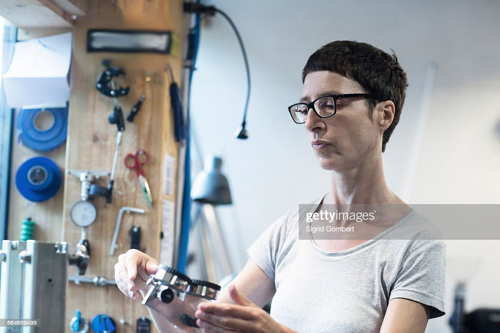 Woman in workshop looking at bicycle part : Stock-Foto