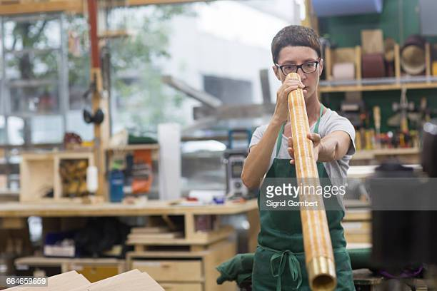 woman in workshop looking through alphorn - sigrid gombert stock pictures, royalty-free photos & images