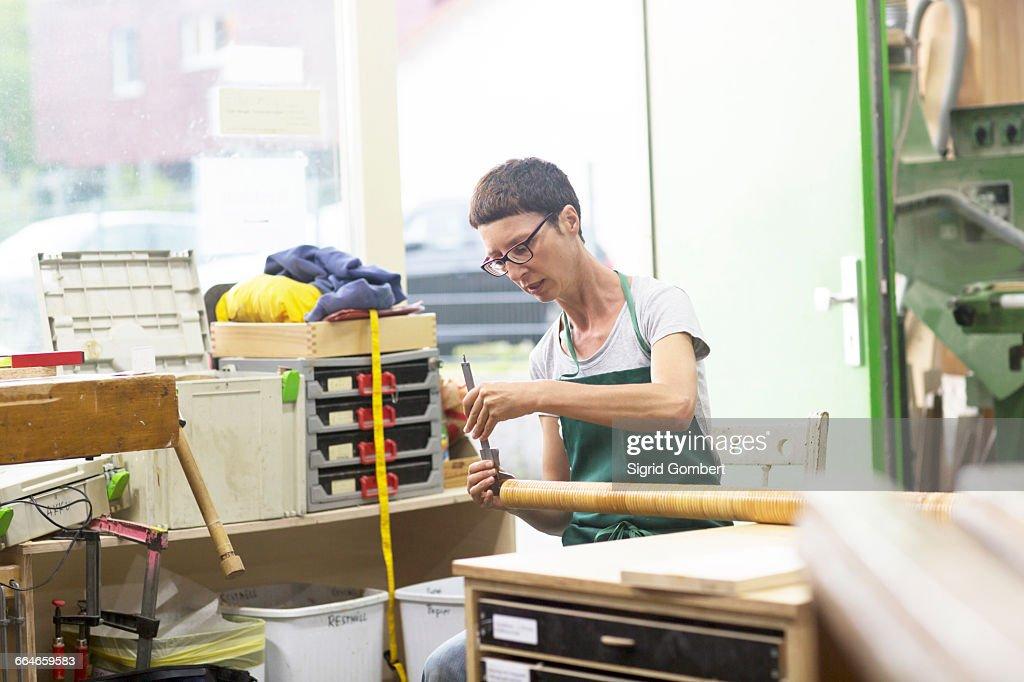 Woman in workshop making alphorn : Stock-Foto