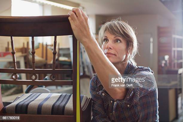 Woman in workshop measuring chair with tape measure