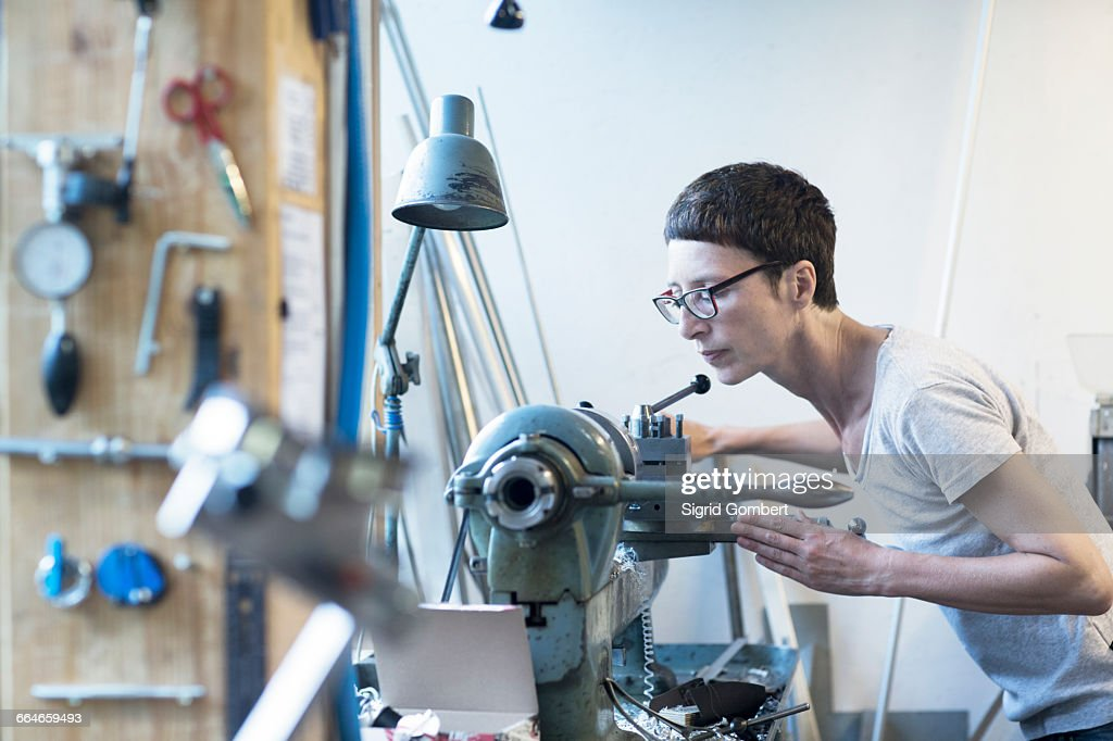 Woman in workshop using machine : Stock-Foto