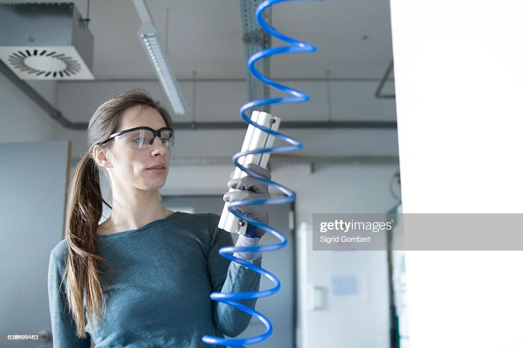 Woman in workshop wearing safety goggles holding control panel : Stock Photo