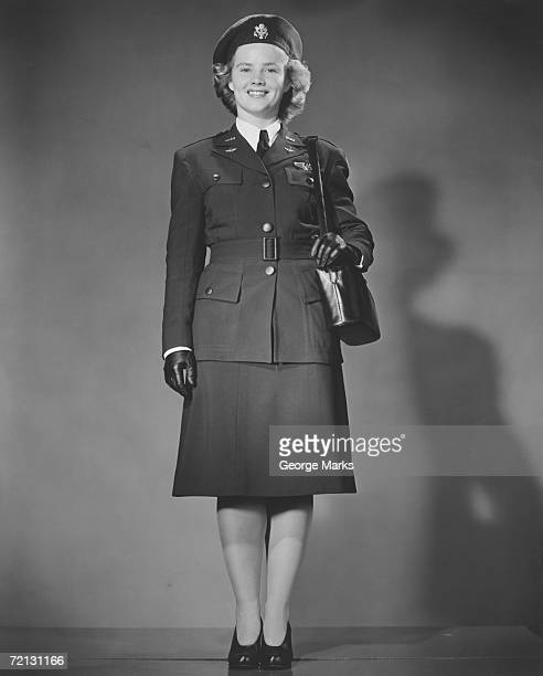 Woman in World War II military uniform posing in studio (B&W), portrait