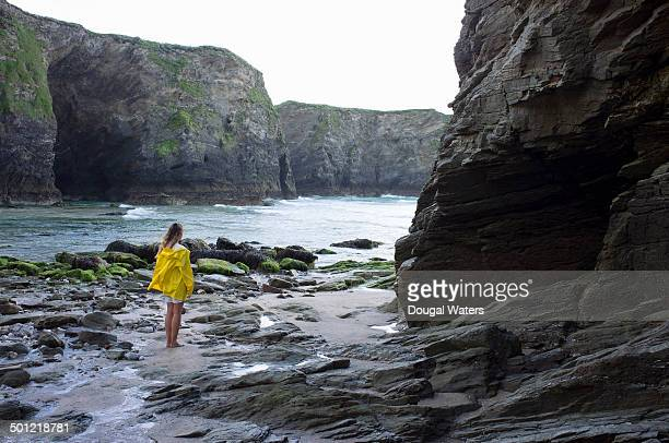 Woman in yellow coat looking out to sea