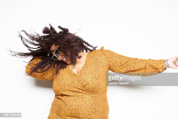 woman in yellow dress dancing in front of white background - plus size model stock pictures, royalty-free photos & images