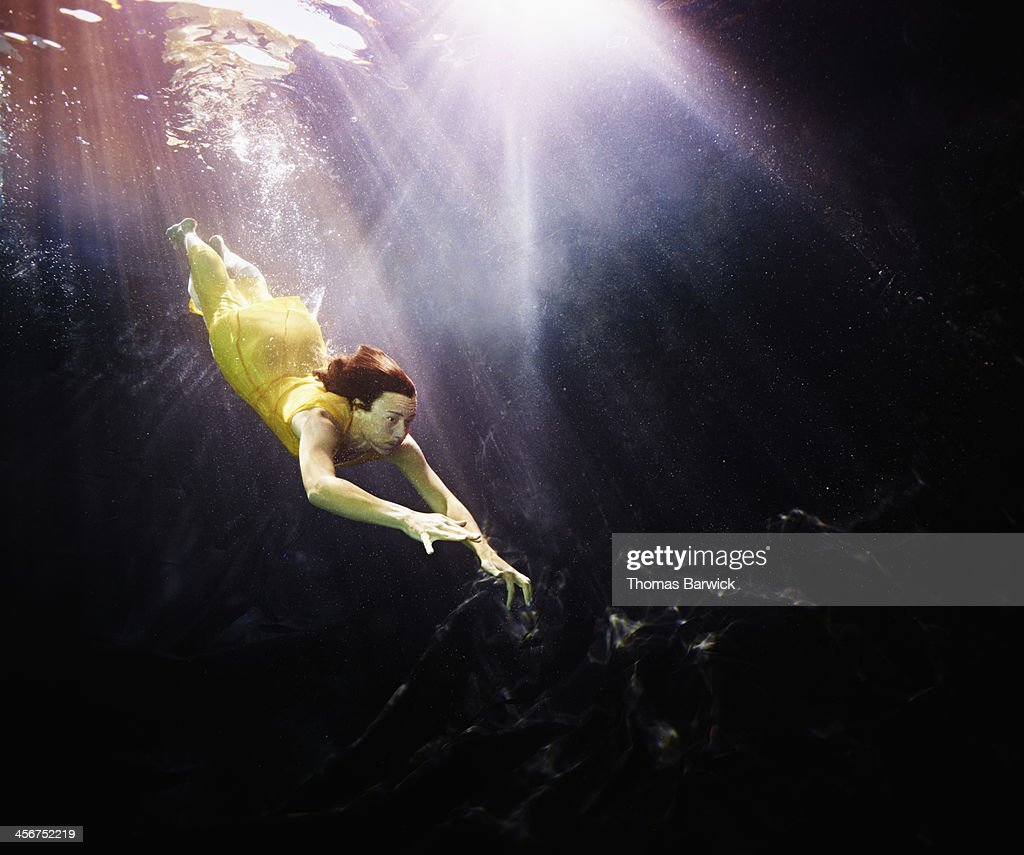 Woman in yellow dress diving underwater : Foto de stock