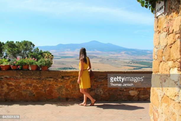 woman in yellow dress looking over the scenic tuscany landscape of val d'orcia from pienza - val d'orcia stock pictures, royalty-free photos & images