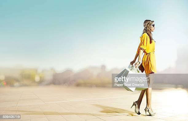 Woman in yellow dress walking by the street