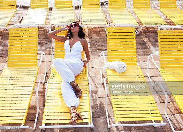 woman in yellow lounge chair - glamour stock pictures, royalty-free photos & images