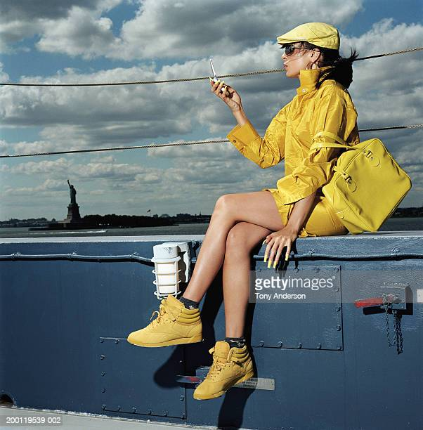Woman in yellow outfit with mobile phone on ferry