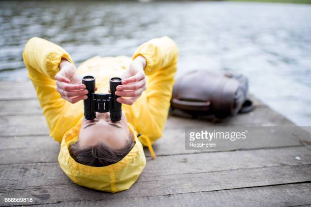 Woman in yellow raincoat lying with binoculars outdoors