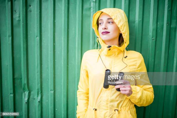 Woman in yellow raincoat on the green background