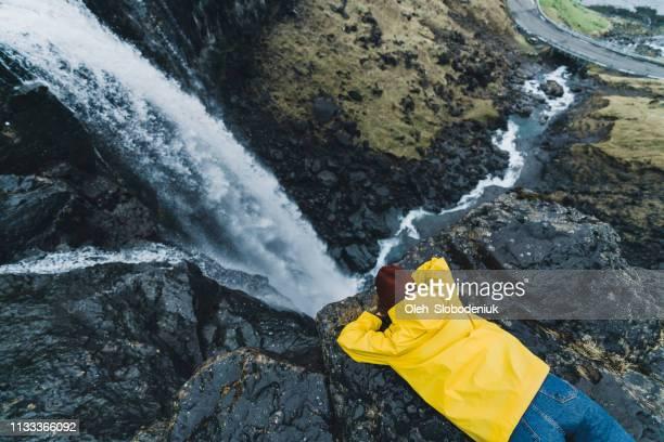 mujer en el impermeable amarillo de pie cerca de la cascada en islas feroe - islas faroe fotografías e imágenes de stock