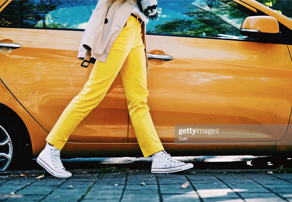 Woman in yellow trousers walking past an orange car : Stock Photo