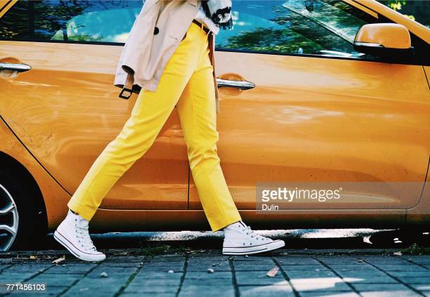 Woman in yellow trousers walking past an orange car