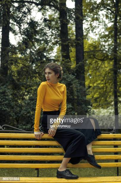 Woman in yellow turtleneck top near the yellow bench in the park