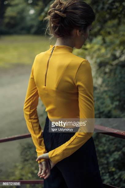 Woman in yellow turtleneck walking in the park