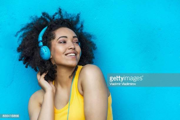 mulher de colete amarelo e azul, fones de ouvido - music - fotografias e filmes do acervo