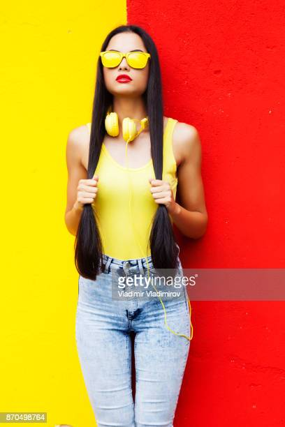 Woman in yellow vest and sunglasses with long hair