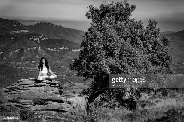 Woman in yoga lotus pose beside tree