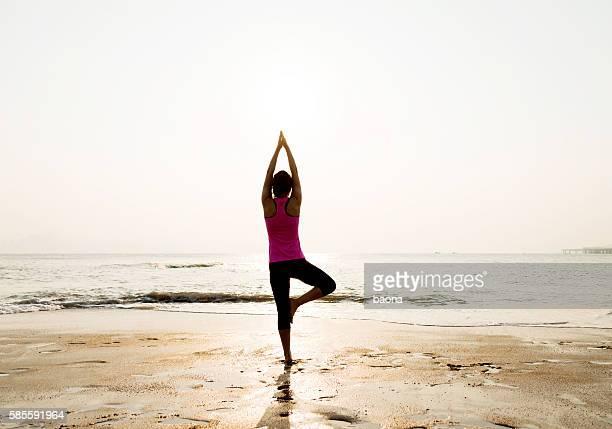 Woman in yoga pose at beach
