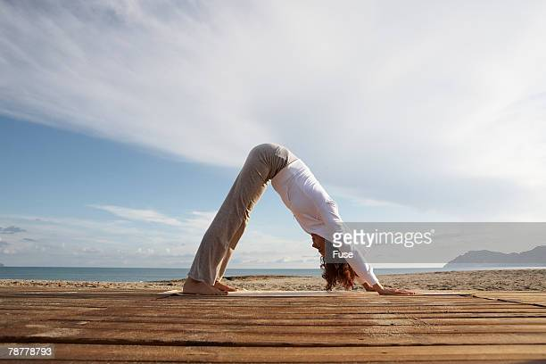 woman in yoga pose at the ocean - older woman bending over stock pictures, royalty-free photos & images
