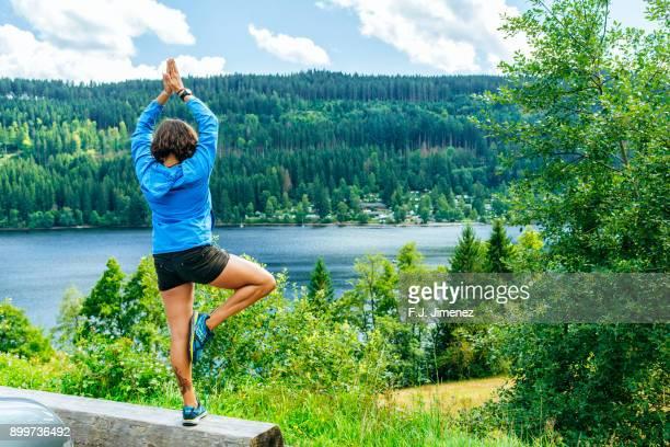 Woman in Yoga pose on Lake Titisee
