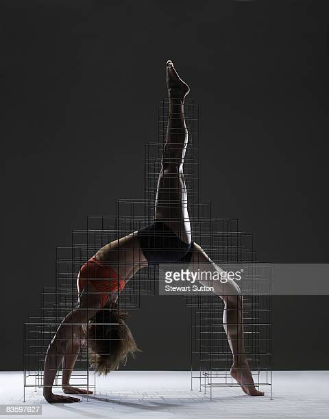 woman in yoga pose supported by armature