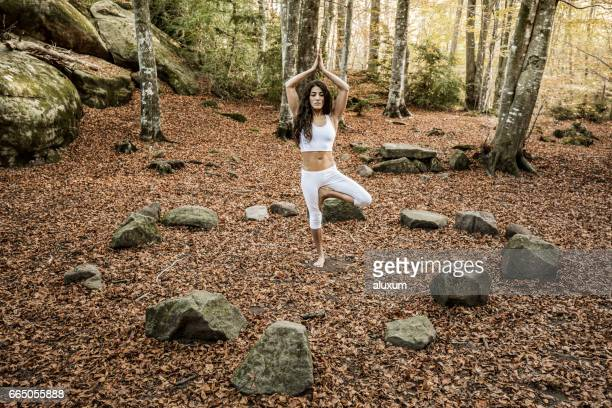 Woman in yoga tree pose inside stone circle