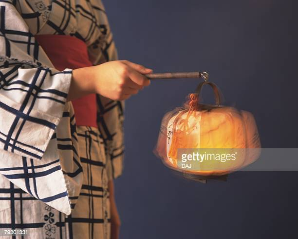 Woman in yukata holding a paper lantern, side view, gray background, blurred motion