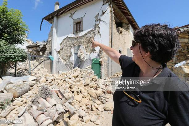 A woman indicates the place where her house was completely collapsed after the earthquake that hit the city of Amatrice in central Italy