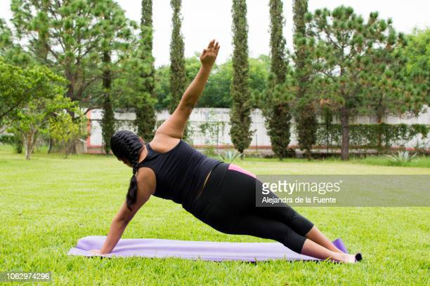 Young woman practicing yoga on her backyard.