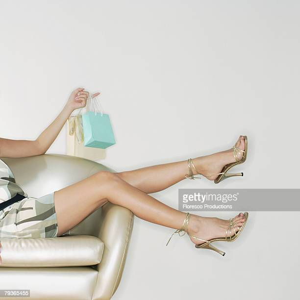 Woman indoors in chair holding shopping bags