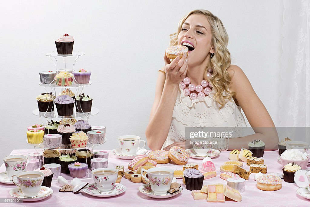 Woman indulging in doughnuts and cakes : Stock Photo