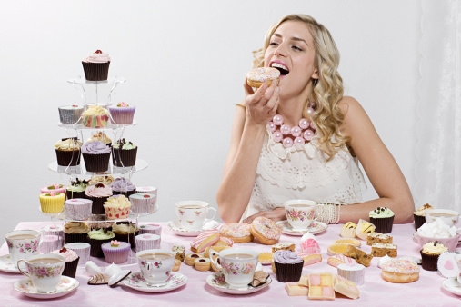 Woman indulging in doughnuts and cakes - gettyimageskorea