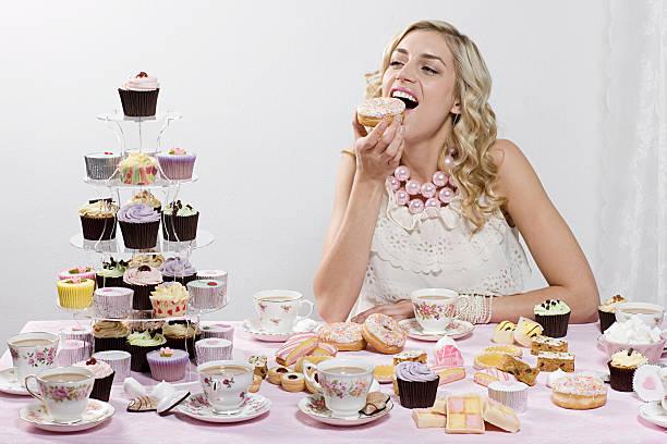woman indulging in doughnuts and cakes - 餐後甜品 個照片及圖片檔