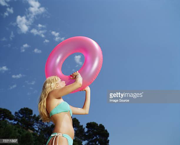 Woman inflating a pink ring