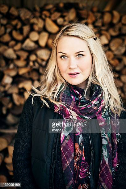 Woman infront of a woodpile