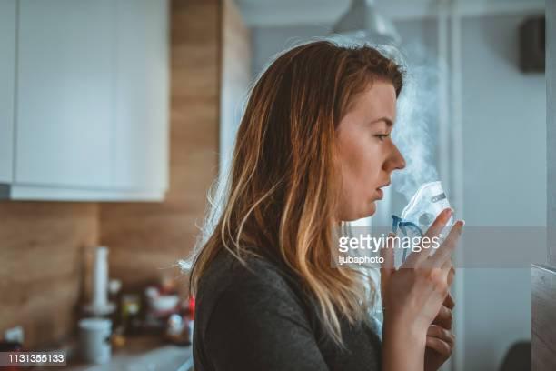 woman inhaling medicine against allergy - amigdalite imagens e fotografias de stock