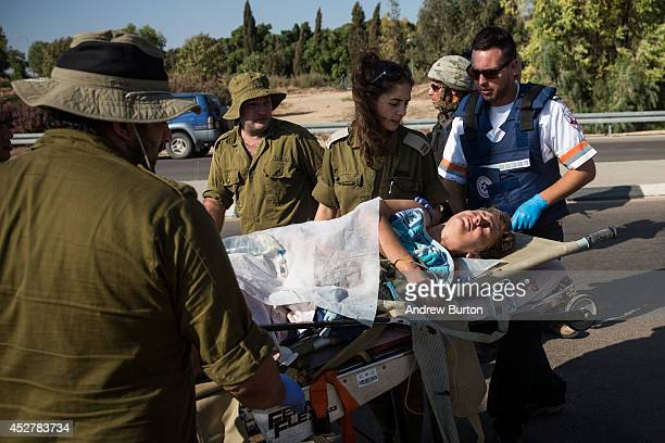 A woman injured in a rocket attack is transferred from a military ambulance to a civilian ambulance on July 27 2014 near Nahal Oz Israel The nearly...