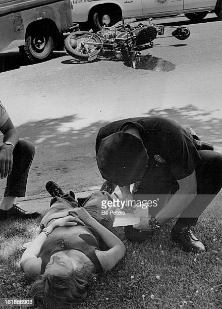 JUN 27 1973 Woman Injured In MotorcycleTruck Collision Unidentified policeman talks to Kandi J Floyd of 835 Sherman St after she was involved in...